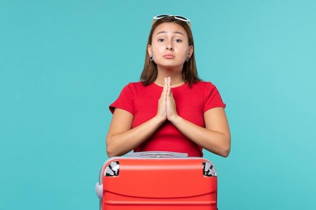 青いスペースで祈って休暇の準備をしている赤いバッグを持つ若い女性の正面図