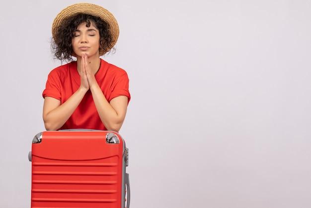 Vista frontale giovane donna con borsa rossa che si prepara per il viaggio pregando su sfondo bianco vacanza colore sole viaggio resto volo turistico aereo
