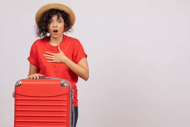 Vista frontale giovane donna con borsa rossa che si prepara per il viaggio su sfondo bianco aereo resto vacanza viaggio turistico colore del sole