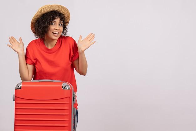 Vista frontale giovane donna con borsa rossa che si prepara per il viaggio su sfondo bianco riposo vacanza colore sole voli turistici viaggio aereo