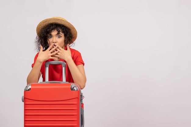 Vista frontale giovane donna con borsa rossa che si prepara per il viaggio su sfondo bianco viaggio sole volo aereo vacanza colore resto
