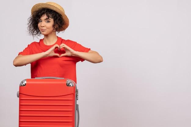Vista frontale giovane donna con borsa rossa che si prepara per il viaggio su sfondo bianco vacanza colore sole viaggio resto volo turistico