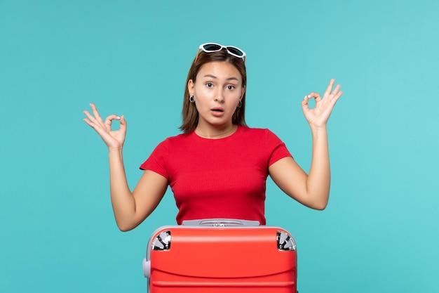 Giovane femmina di vista frontale con il sacchetto rosso che prepara per la vacanza sullo scrittorio blu