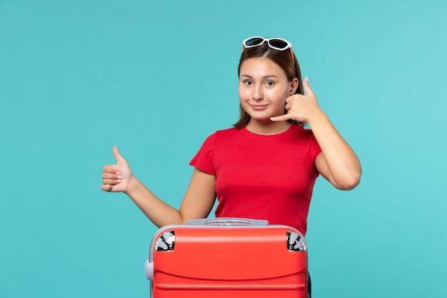 Giovane femmina di vista frontale con la borsa rossa che prepara per la vacanza sul viaggio di viaggio di vacanza di viaggio del mare del pavimento blu