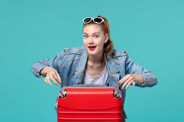 Giovane femmina di vista frontale con il sacchetto rosso che prepara per la vacanza sullo spazio blu