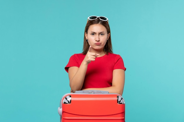 Front view young female with red bag preparing for vacation on a blue space