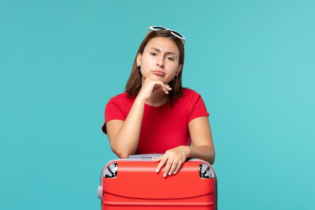 Front view young female with red bag preparing for vacation on blue space