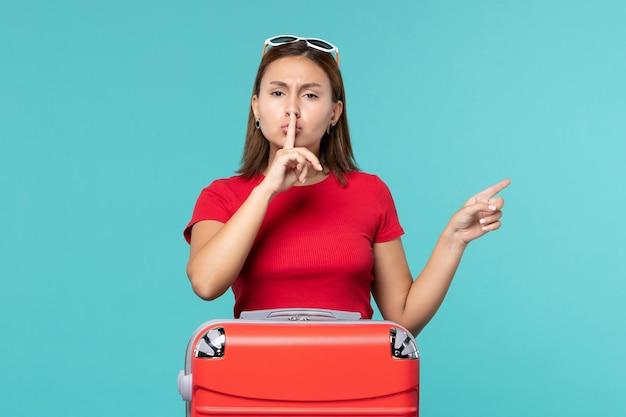 Giovane femmina di vista frontale con il sacchetto rosso che prepara per la vacanza sullo spazio blu-chiaro