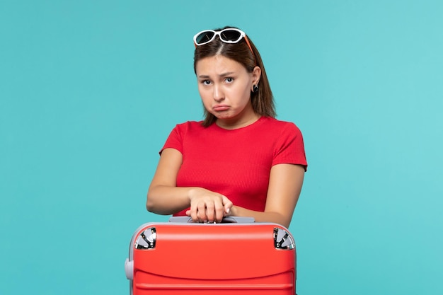 Front view young female with red bag preparing for vacation on light blue space