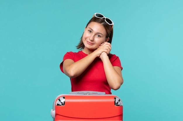 Giovane femmina di vista frontale con il sacchetto rosso che prepara per la vacanza e il sorriso sullo spazio blu
