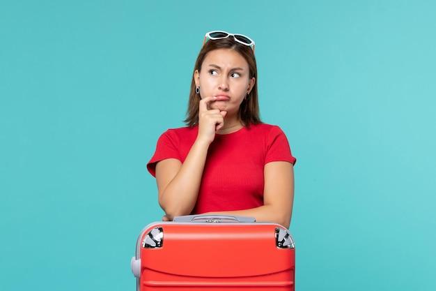 Giovane femmina di vista frontale con il sacchetto rosso che prepara per le vacanze e pensa sullo spazio blu