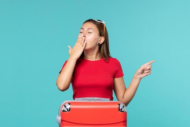 Giovane femmina di vista frontale con il sacchetto rosso che prepara per la vacanza che sbadiglia sullo spazio blu