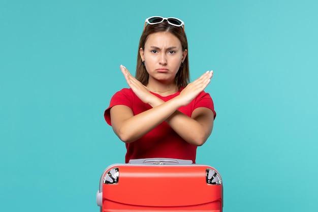 青いスペースに禁止サインを示す赤いバッグと正面図若い女性