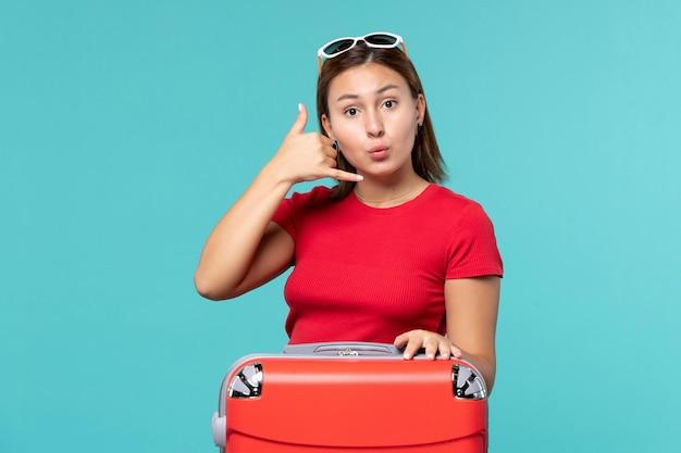 Giovane femmina di vista frontale con il sacchetto rosso che mostra il segnale di chiamata telefonica sullo spazio blu
