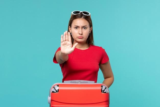 푸른 공간에 정지 신호를 보여주는 빨간 가방 전면보기 젊은 여성