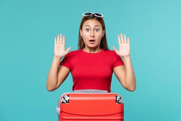 Giovane femmina di vista frontale con il sacchetto rosso e l'espressione sorpresa sullo spazio blu
