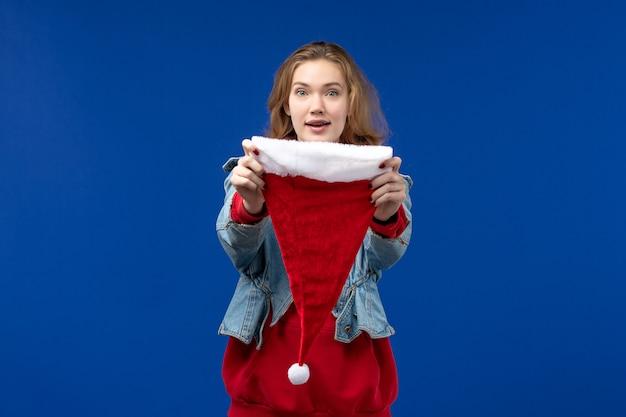 Giovane femmina di vista frontale con il cappuccio rosso sul nuovo anno di colore di natale di festa dello scrittorio blu