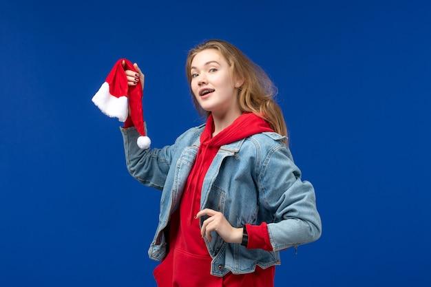 Вид спереди молодая женщина с красной кепкой на синем фоне праздники рождество новый год