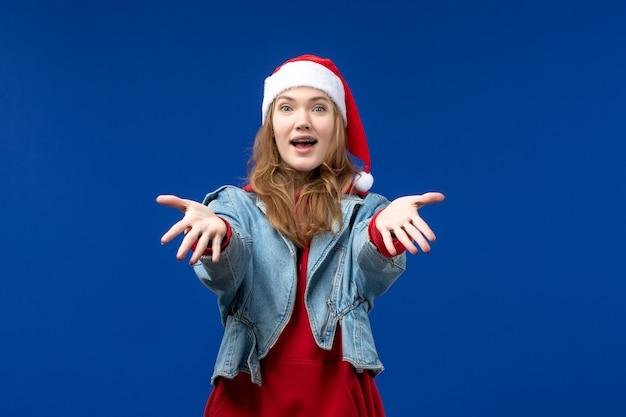 파란색 배경 새 해 휴일 크리스마스에 빨간 모자와 전면보기 젊은 여성