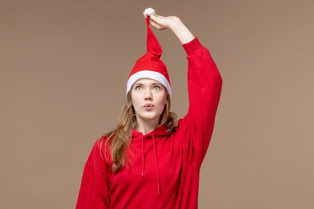Giovane femmina vista frontale con mantello rosso su sfondo marrone vacanze di natale emozione
