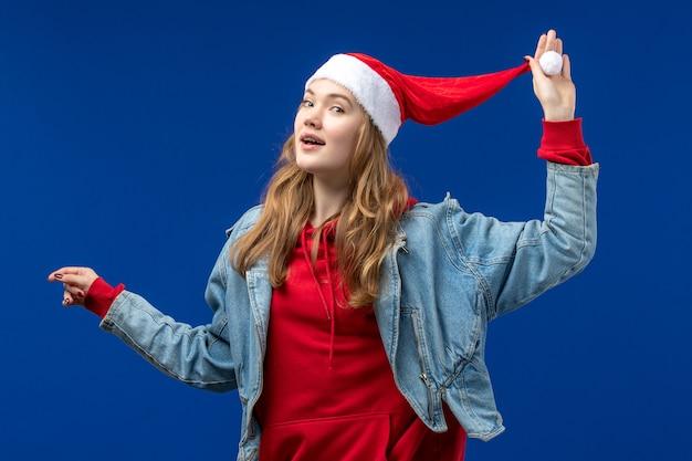 Giovane donna di vista frontale con cappuccio rosso di natale sull'emozione di colore di natale del fondo blu