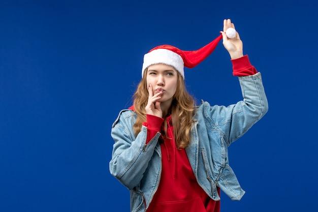 Giovane femmina di vista frontale con cappuccio rosso di natale sulle emozioni di colore di natale sfondo blu