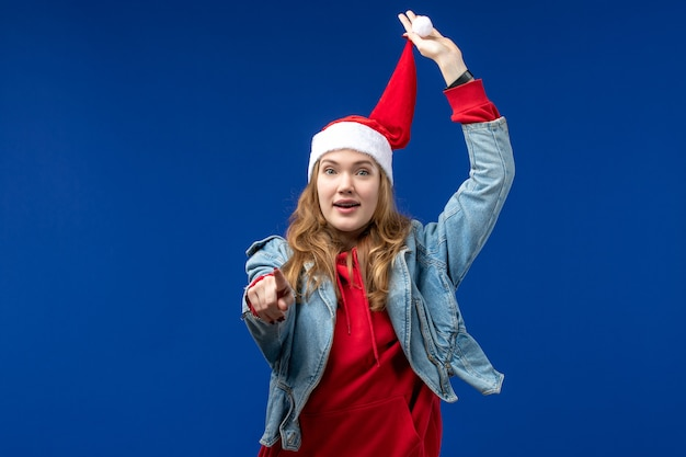 Front view young female with red christmas cap on the blue background christmas color emotions