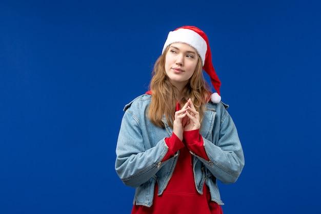 Vista frontale giovane femmina con tappo rosso di natale su sfondo blu vacanze di natale emozione