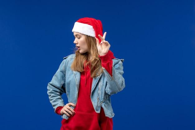 Giovane femmina di vista frontale con cappuccio rosso di natale su uno spazio blu