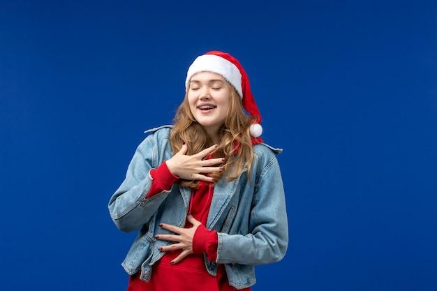 파란색 배경 감정 크리스마스 색상에 빨간 크리스마스 모자와 전면보기 젊은 여성