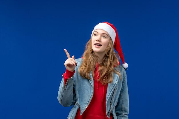 파란색 배경 감정 크리스마스 휴일에 빨간 크리스마스 모자와 전면보기 젊은 여성