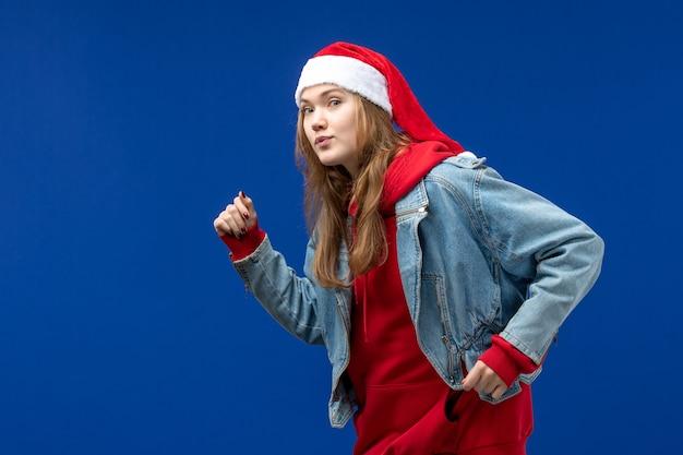 Вид спереди молодая женщина с красной рождественской шапкой на синем фоне эмоции рождественского праздника
