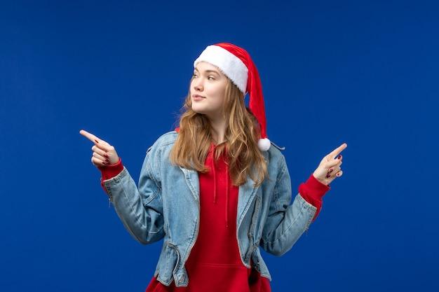 青い机の上の赤いクリスマスキャップと正面図若い女性クリスマス感情色