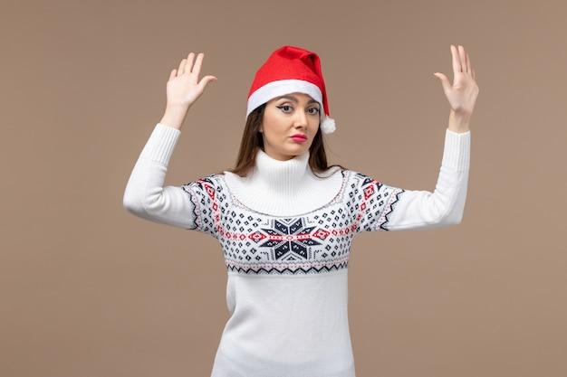Вид спереди молодая женщина с красной рождественской шапкой на коричневом фоне рождественские праздничные эмоции