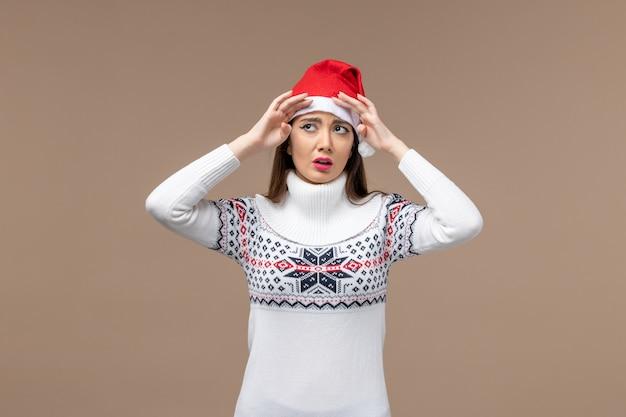 茶色の背景感情クリスマス休暇に悲しい顔を持つ若い女性
