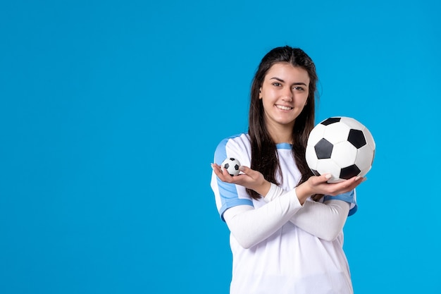 Front view young female with soccer ball on blue wall