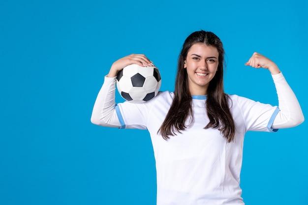 Giovane donna di vista frontale con pallone da calcio sulla parete blu