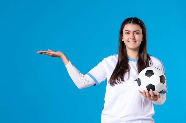 Вид спереди молодая женщина с футбольным мячом на синей стене