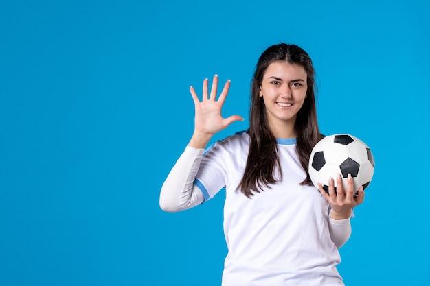 青い壁にサッカーボールの正面図若い女性