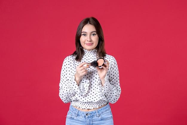 Vista frontale della giovane donna con nappa e polvere per il trucco sulla parete rossa