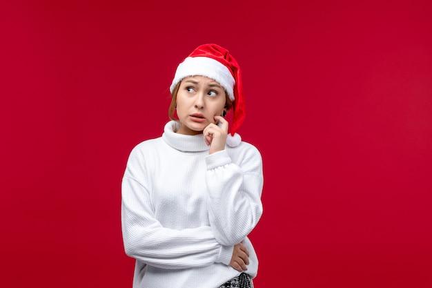 Vista frontale giovane femmina con espressione di pensiero su sfondo rosso
