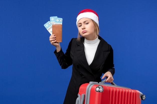 Giovane femmina di vista frontale con i biglietti e la borsa sulla vacanza di feste dell'aereo della parete blu