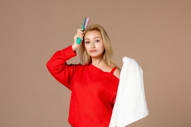 Vista frontale giovane femmina con asciugamano e spazzola per capelli su sfondo rosa scuro