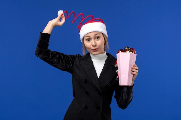 Giovane femmina di vista frontale con i giocattoli dell'albero sul giocattolo di festa del nuovo anno di emozione della parete blu