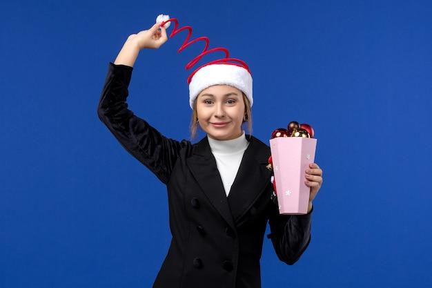Giovane femmina di vista frontale con i giocattoli dell'albero sul giocattolo blu di feste di nuovo anno di emozione della parete