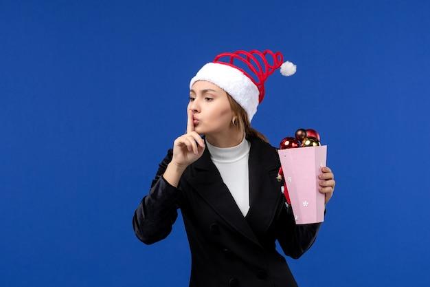 Giovane femmina di vista frontale con i giocattoli dell'albero sul colore di emozioni di festa del nuovo anno della parete blu