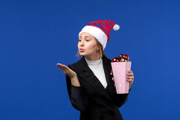 青い壁の色の新年の休日の感情に木のおもちゃと正面図若い女性