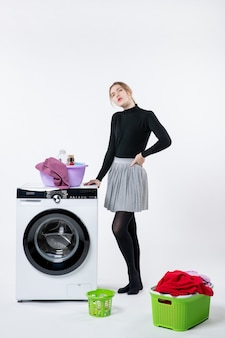 Front view of young female with washer and dirty clothes on a white wall