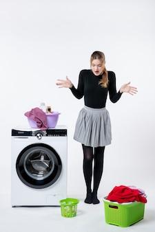 Vista frontale della giovane donna con lavatrice e vestiti sporchi sul muro bianco white
