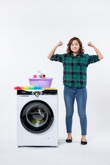 흰색 벽에 세탁기와 샴푸를 구부리는 전면 보기 젊은 여성